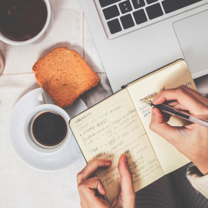 En hånd skriver i en notesbog ved en computer