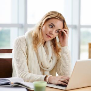 Eftertænksom kvinde ved computer