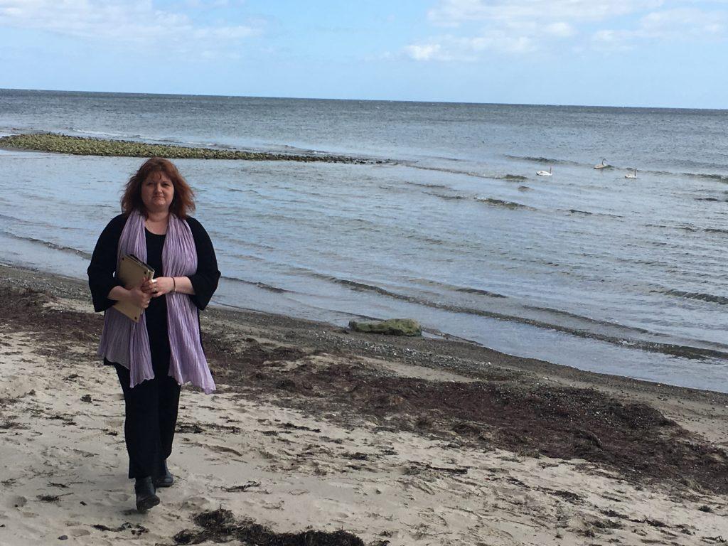Forfatter Gittemie Eriksen går ved stranden
