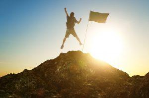 succesfuld mand på toppen af et bjerg